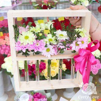 Хризантемы в колбе на деревянной подставке